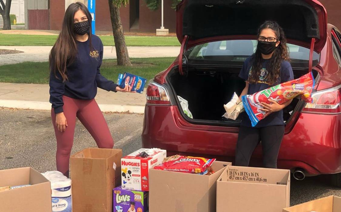 two students with donation items by car